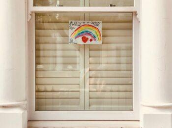 In einer Fensterscheibe ist ein gemalter Regenbogen zu sein. Er symbolisiert Verbundenheit und gibt Trost in der Corona-Pandemie.