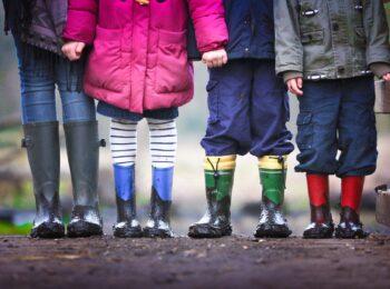 Vier Kinder stehen in bunten Gummistiefeln nebeneinander auf der Strasse.