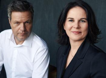 Das Foto zeigt Annalena Baerbock und Robert Habeck vor einem schwarzen Hintergrund.