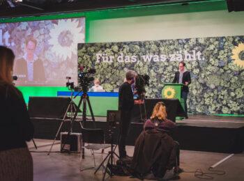 Das Bild zeigt die Bühne des Landesparteitags, Steffen Regis am Redepult und ein Fernsehteam.
