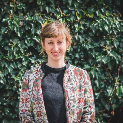 Das Foto zeigt Selma Beck. Sie steht vor einer grünen Hecke.