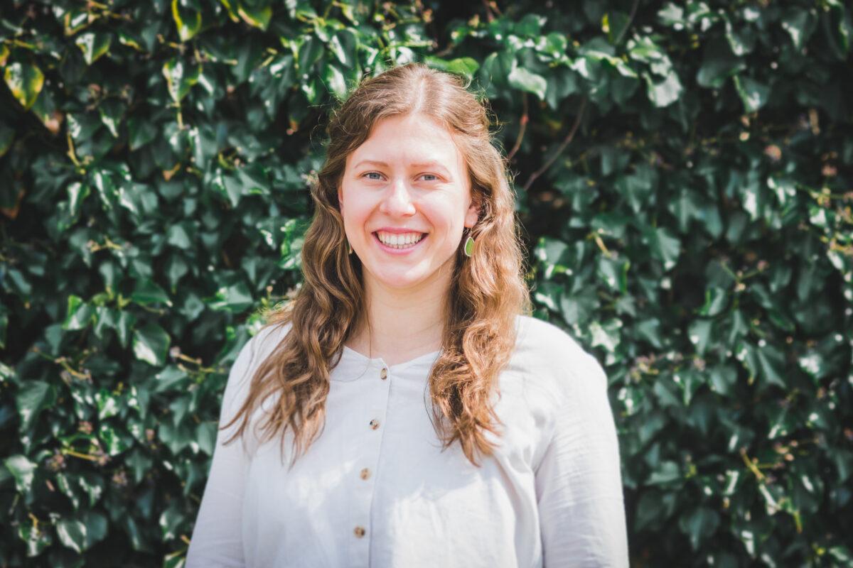 Das Foto zeigt Mayra Vriesema. Sie steht vor einer grünen Hecke.