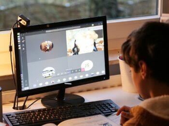 Das Foto zeigt einen jungen Schüler, der zuhause lernt und per Videokonferenz am Unterricht teilnimmt.